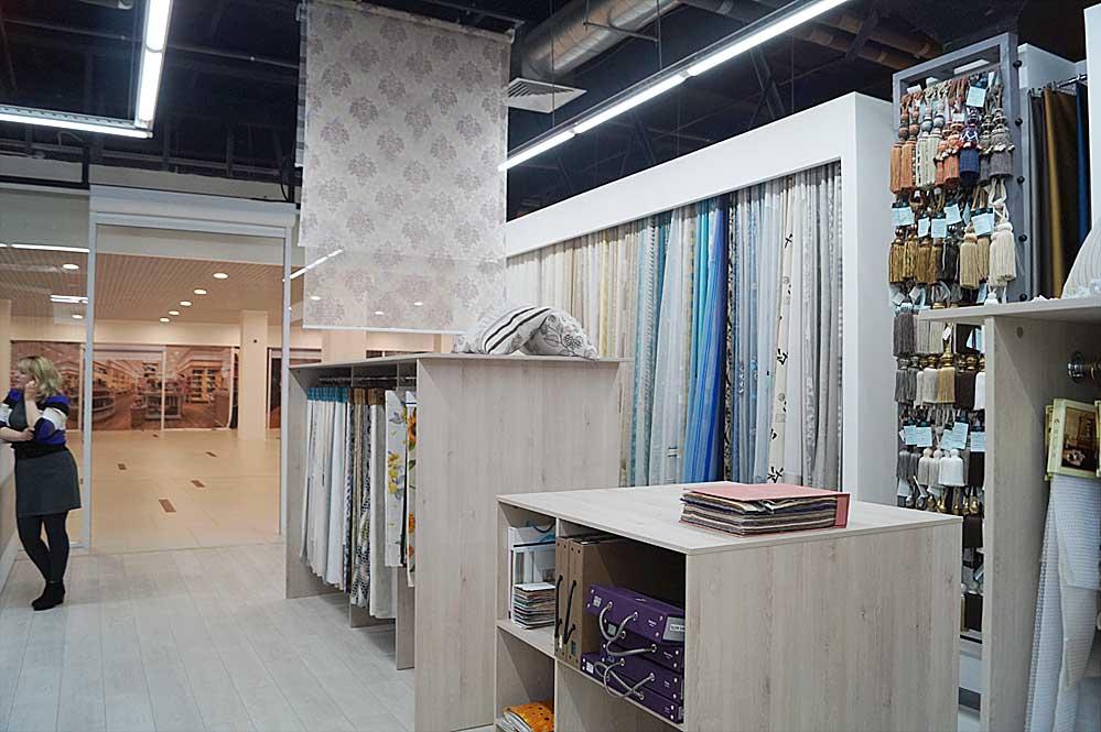 Слева от входа ткани для штор, заказные коллекции текстиля и рулонные шторы моторизованные с пультом ДУ