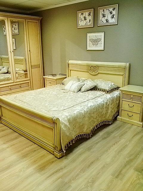 Шелковое покрывало и декоративные подушки ручной работы подчеркивают теплый тон традиционной деревянной мебели спальни и двуспальной кровати.