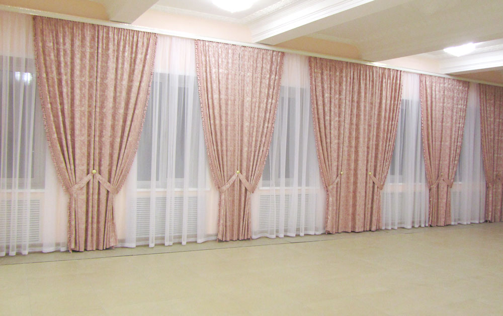 Простой дизайн и крсивый эффект дают розово-коралловые шторы в зале с большим количеством окон