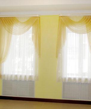 Легкие желтые занавески из органзы с ярко-выраженным асимметричным дизайном поднимают настроение всем в офисе!