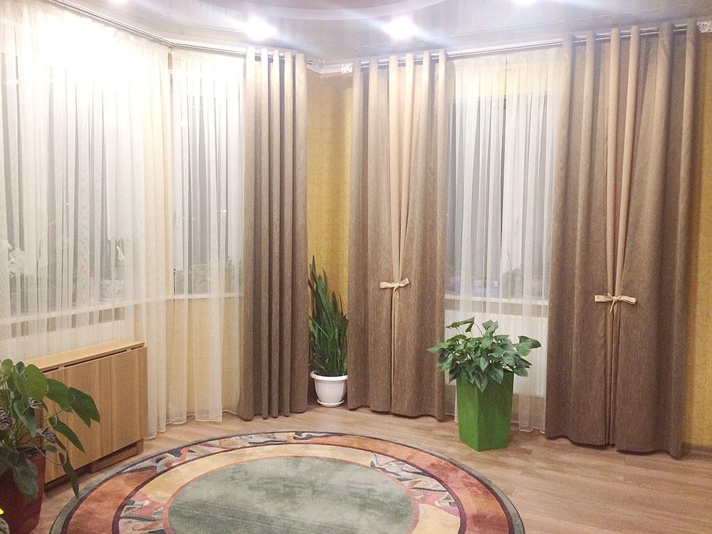 Зал с коричневыми шторами и эркерными окнами.