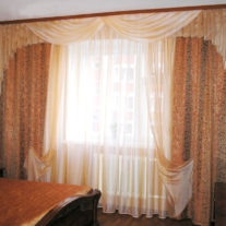 Общий вид спальни с золотисто-оранжевыми занавесками