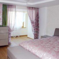 Прозрачные легкие занавески и декоративная панель с розами вбольшой спальне