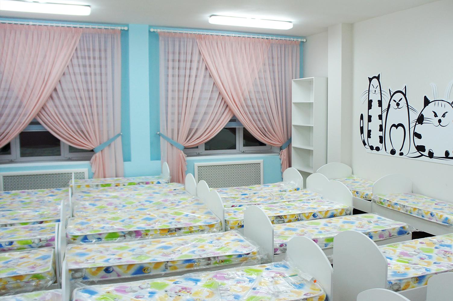 Оформление спальни детсада- розовые занавески с голубыми рулонными шторами зебра