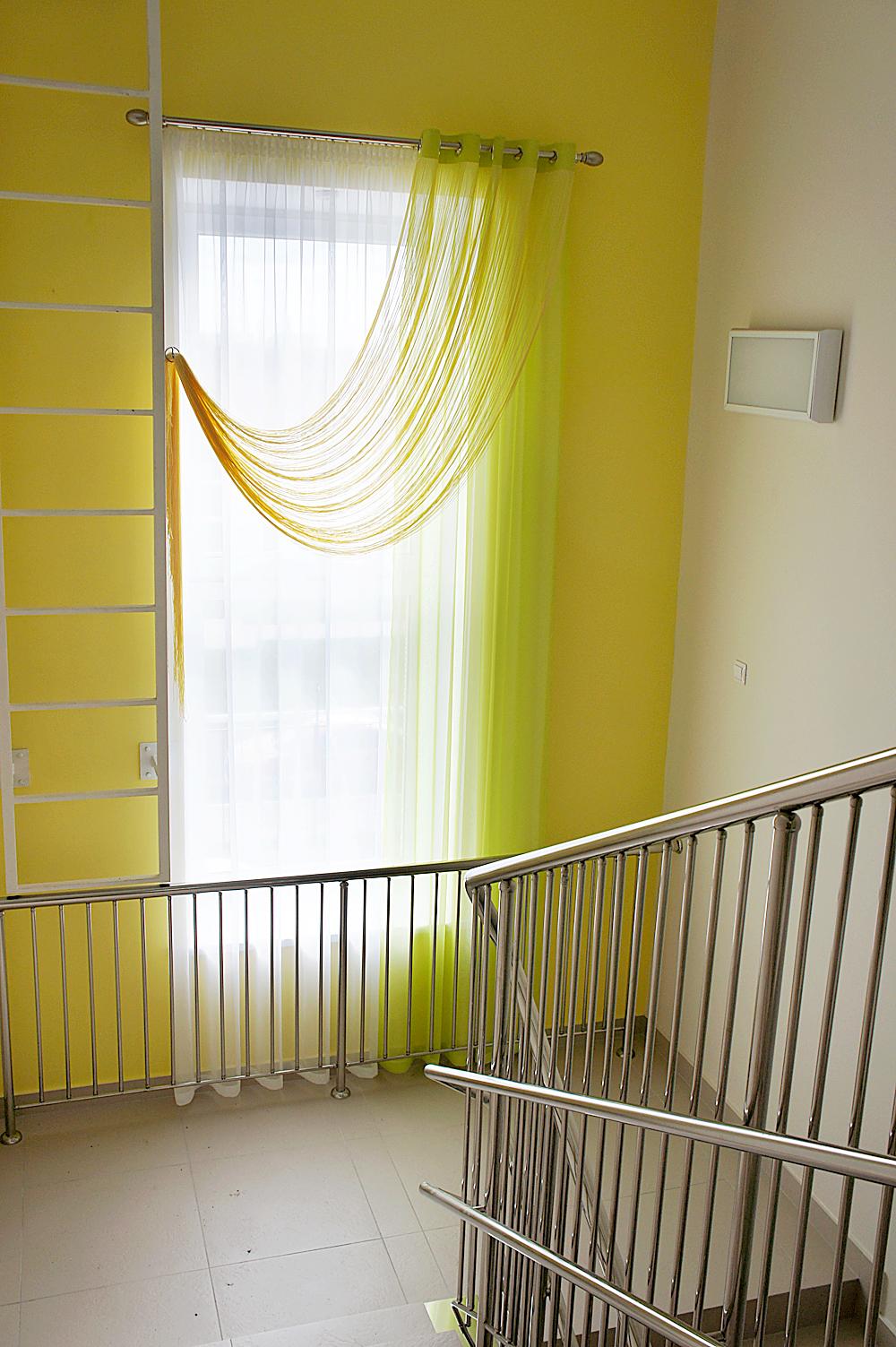 Очень большое окно на лестничной клнтке оформлено ярко-желтой кисеей на классическом настенном карнизе